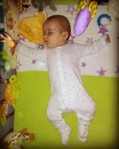 bebe-dormind-in-pat-cu-carusel-de-patut